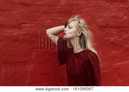 Beautiful blond woman blowing kisses against red wall