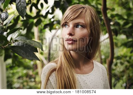 Beautiful blond woman with blue eyes in garden