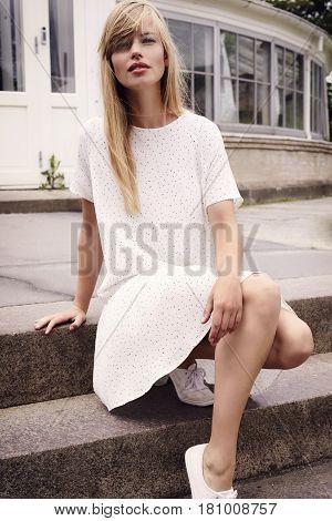 Portrait of beautiful woman in summer dress  on steps