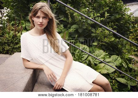 Woman in white  in summer dress on steps portrait