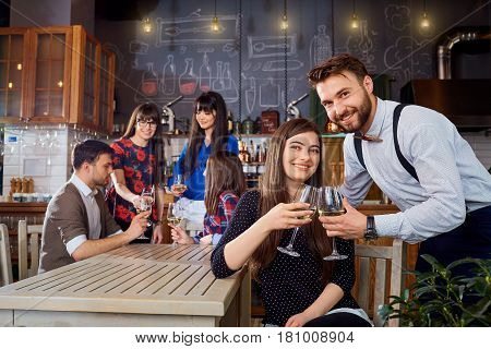Meeting friends at the bar restaurant. A couple of men and  girl chat in cafe.