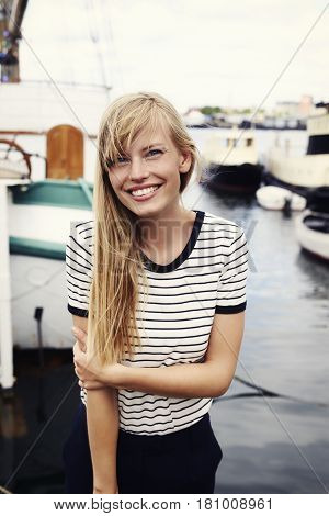 Stunning blond woman smiling at camera on harbour