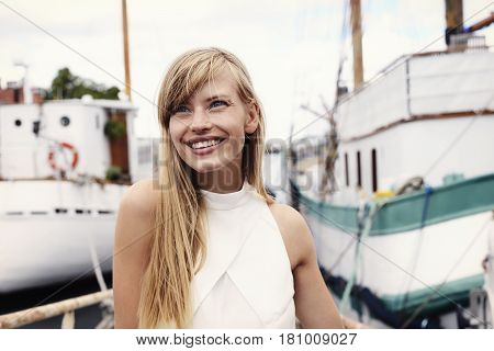 Blue eyed blond woman in boatyard smiling