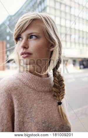 Blue eyed girl in city looking away