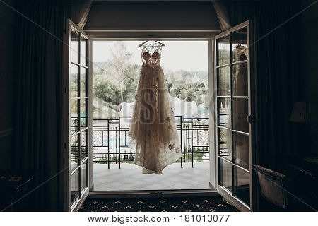 luxury wedding dress hanging on window in a hotel room. silhouette of amazing bride's gown in light. morning preparation getting ready. space for text . wedding morning