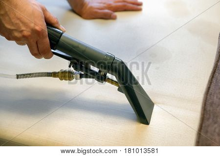 Cleaning couch with steam cleaner - detail