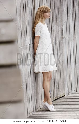 Beautiful blond in white dress looking away
