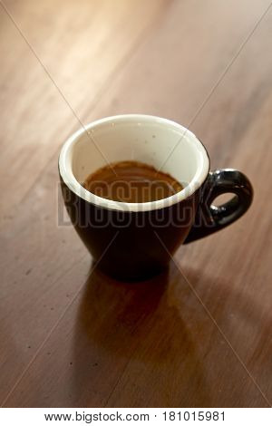 Black cup of coffee on old wooden table
