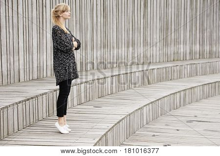 Blond woman standing on wooden step looking away
