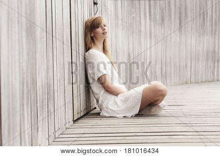 Beautiful woman sitting in white dress portrait
