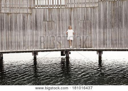 Woman wearing summer dress in wooden pier portrait