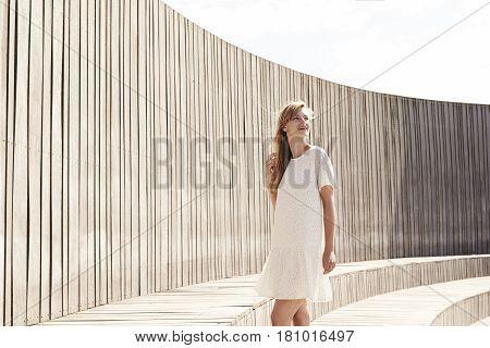 Beautiful woman wearing summer dress  in sunlight looking away