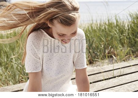 Beautiful woman wearing summer dress with windswept blond hair
