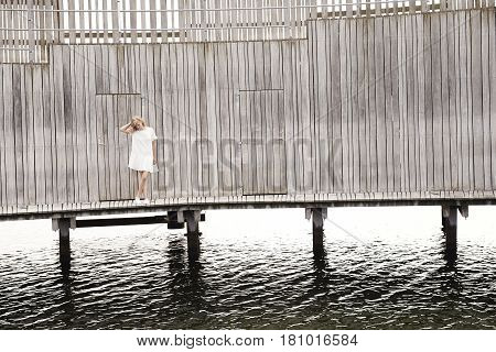 Woman standing on wooden pier over water