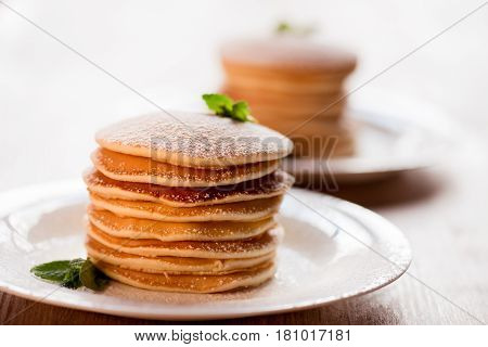 Tasty Pancakes With Mint And Powdered Sugar On White Plates
