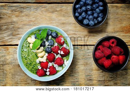 Spinach smoothies breakfast bowl with coconut flakes raspberry blueberry and cashews.