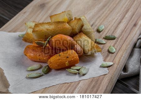 Quick light snack. Croutons and baked carrots on a kitchen board