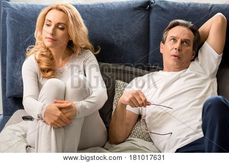 Upset Middle Aged Couple Quarreling And Lying On Bed At Home