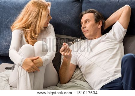 Upset Middle Aged Couple Talking, Looking At Each Other And Lying On Bed At Home