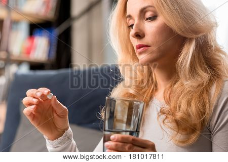 Blonde Middle Aged Woman Holding Glass With Water And Pill At Home