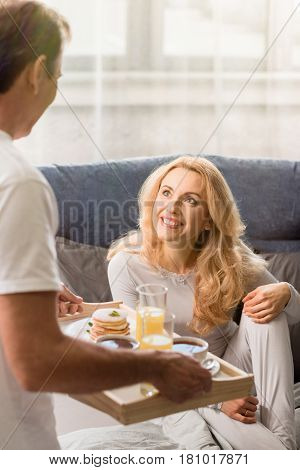 Man Bringing Tray With Tasty Breakfast To Happy Blonde Woman On Bed