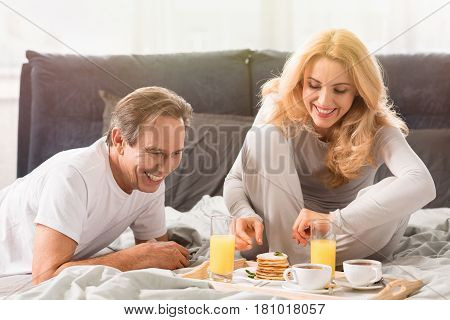 Happy Middle Aged Couple Eating Pancakes Together In Bed