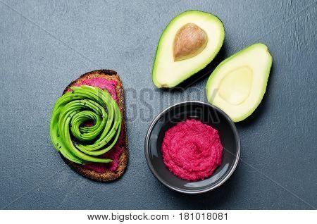 Healthy beet hummus avocado rye breakfast sandwich.