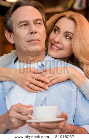 Beautiful Smiling Blonde Woman Hugging Pensive Mature Man Holding Tea Cup