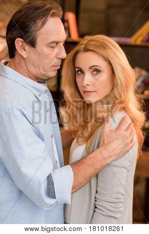 Side View Of Serious Mature Man Hugging Beautiful Pensive Woman