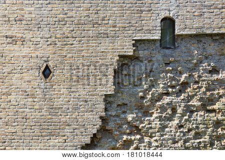 Old wall of medieval castle made of white bricks and stone