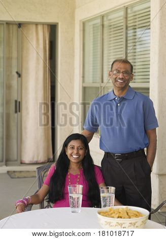 Indian man standing next to wife on patio