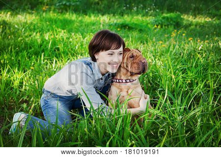 Happy young woman playing with dog Shar Pei in the green grass. True friends forever people and pets concept.