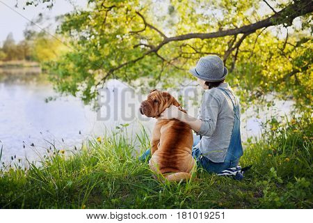 Young woman in hat with dog Shar Pei sitting in the field and looking to the river. True friends forever people concept. Meditation and relaxation back to camera.