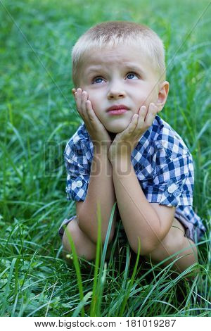 Portrait of cute little boy with a sad eyes sitting on the green lawn.