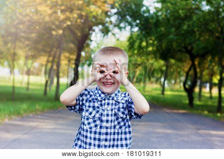 Сute little child boy with a happy laugh making glasses out of his hands in beautiful autumn park.