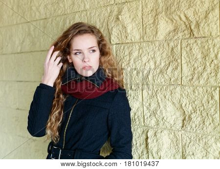 Young fashion woman girl model with long curly hair looking into the distance and posing outdoor near the wall in the street background. Sensual look, warm toned.