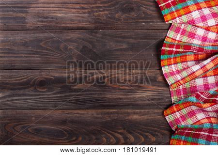 Red checkered tablecloth on a dark wooden table with copy space for your text. Top view.