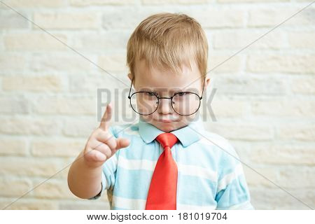 Serious boy standing with a finger in big glasses. The concept of the evil boss