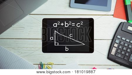 Digital composite of Directly above shot of formula in smart phone with technologies and office supplies on wooden table