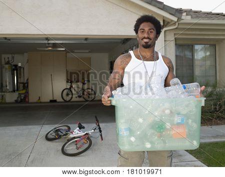 African man carrying recycling bin