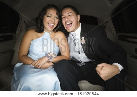 Hispanic teenaged couple laughing in limousine