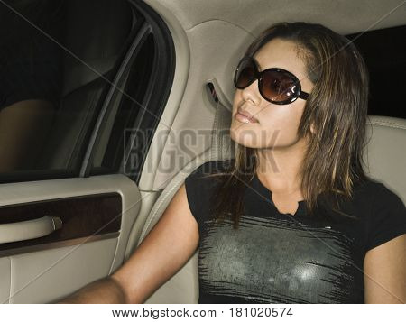 Hispanic teenaged girl sitting in limousine