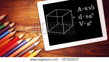 Digital composite of Directly above shot of formula in digital tablet with color pencils on wooden table