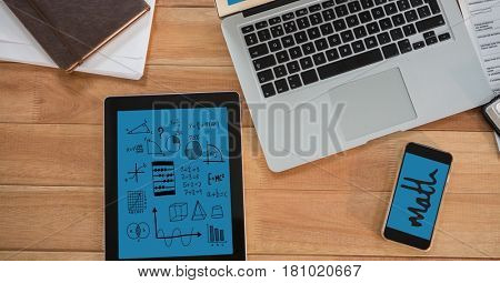 Digital composite of Directly above shot of technologies with diary and papers on wooden table