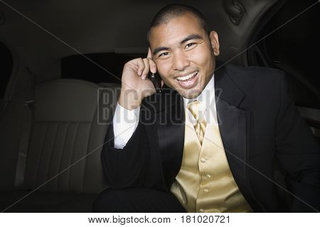 Asian man talking on cell phone in limousine