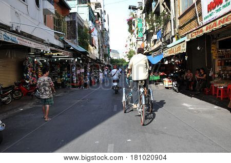 HO CHI MINH VIETNAM - FEBRUARY 15 2013: Tourist taking a tour with a classic Vietnamese rickshaw tuk tuk in Saigon