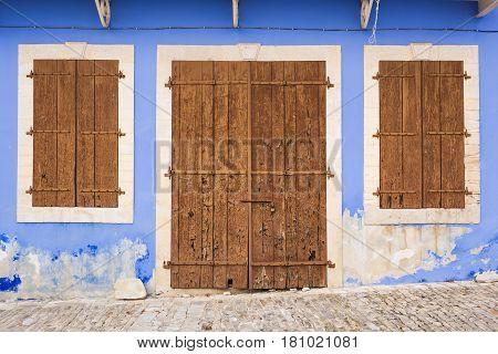 Old wooden door with metal hinges and lock.
