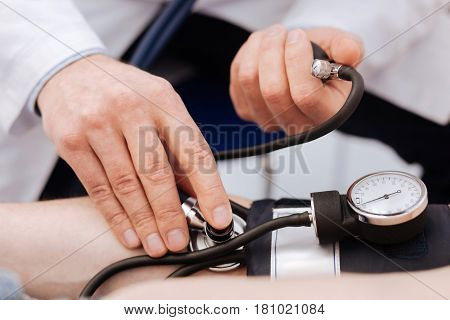 Checking the correctness. Busy prominent private physician running a test on his patient using special equipment for measuring his blood pressure