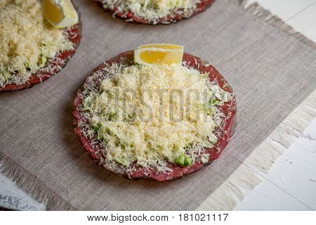 Carpaccio from beef with greens and cheese on a plate on a gray background