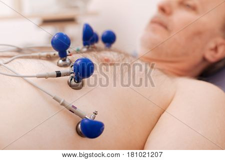 Medical procedure. Calm ill retired man lying still on medical bed with some sensors attaching to his chest for checking how his heart functioning